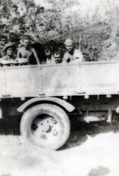 """After the battle of Namur, 1/24 was ordered to clean up its battlefield. """"We found an old flatbed truck and managed to get it started. We got the bright idea to use it to haul bodies."""" Disgust is evident on every face, despite the blurred focus."""