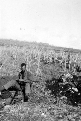 Sergeant Olin England, mortar section, in the field on Saipan. The excavation at right is probably a mortar pit.