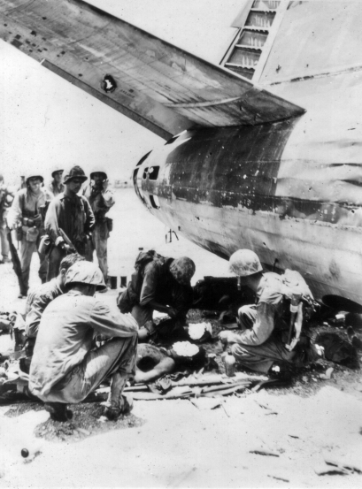 An advance aid station set up in the shelter of a wrecked Japanese bomber on Roi. These wounded men from the 23rd Marines have had their faces blanked out by a wartime censor.