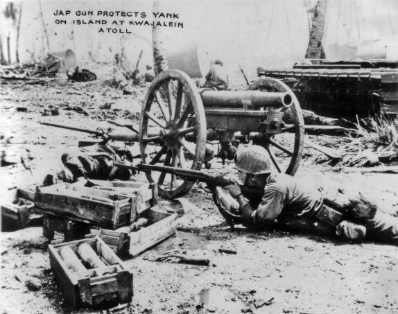 A GI takes cover near a small Japanese artillery piece.