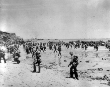 Additional waves of marines come ashore. The fact that these men are walking in standing up indicates that they are not the first to cross this beach.