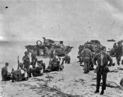 Marine and Army troops rest on an invasion beach. The amphibious tank in the background has been hit by something which has caused its ammunition to explode, destroying the machine from the inside.