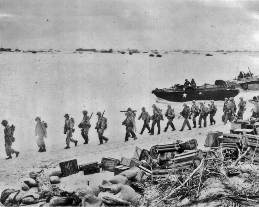 Marines move down a beach littered with supplies. Date and location unknown.