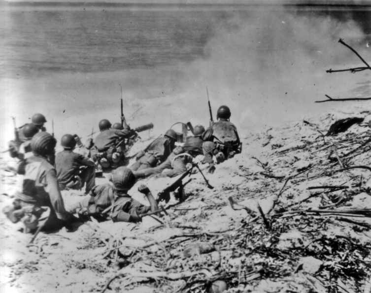 A heavy machine gun from Third Battalion, 22nd Marines fires down the beach on Eniewetok, Kwajalein. Army troops with a BAR observe the results of marine fire.