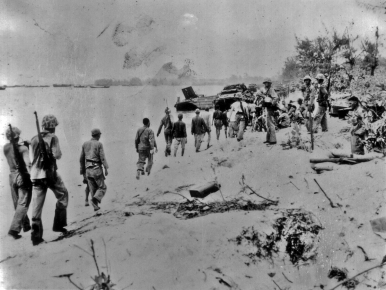 A rare circumstance - Japanese prisoners escorted along a beach by their American captors.