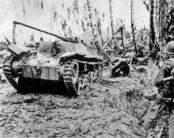 Marines cautiously inspect a destroyed Japanese tank.