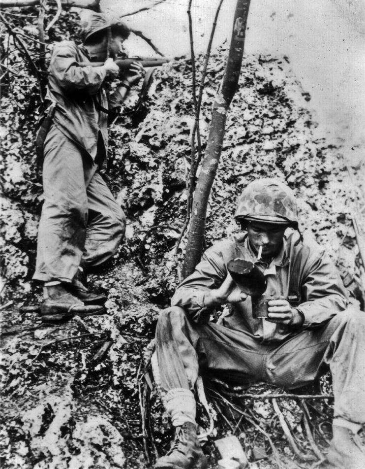 As one marine keeps watch, his buddy takes a brief break for water and a spell off his feet. Peleliu, 1944.