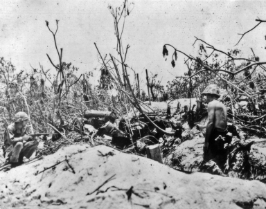 As a marine with a carbine covers the entrance, a pistol-toting officer moves up to clear out a bunker.