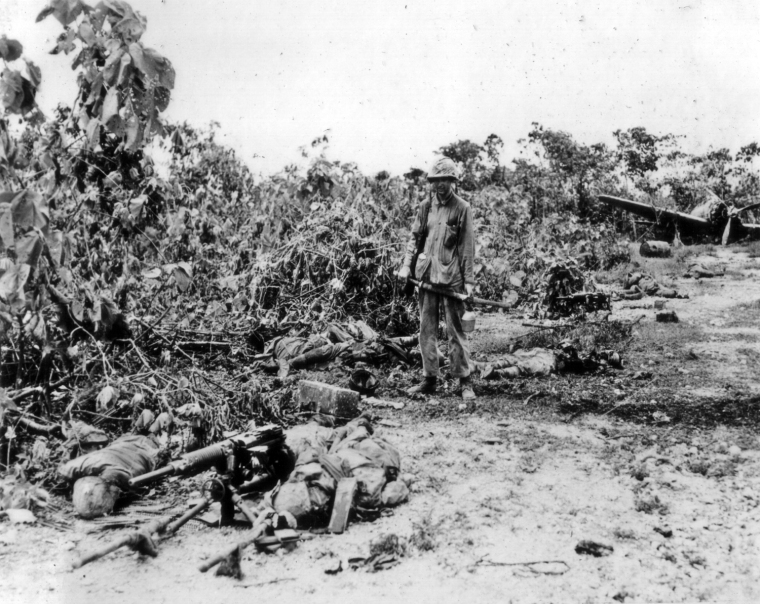 The scene of a bitter fight. Two Japanese machine guns have been eliminated, as has a Japanese aircraft in the background. The marine is carrying a Samurai sword, probably a souvenir of this incident.