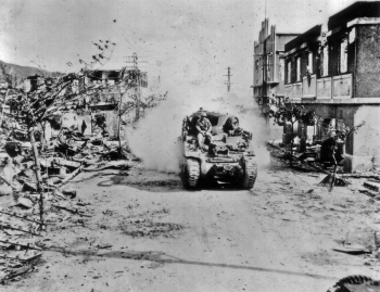 Marines on tanks ride through the town of Garapan, Saipan in July, 1944.