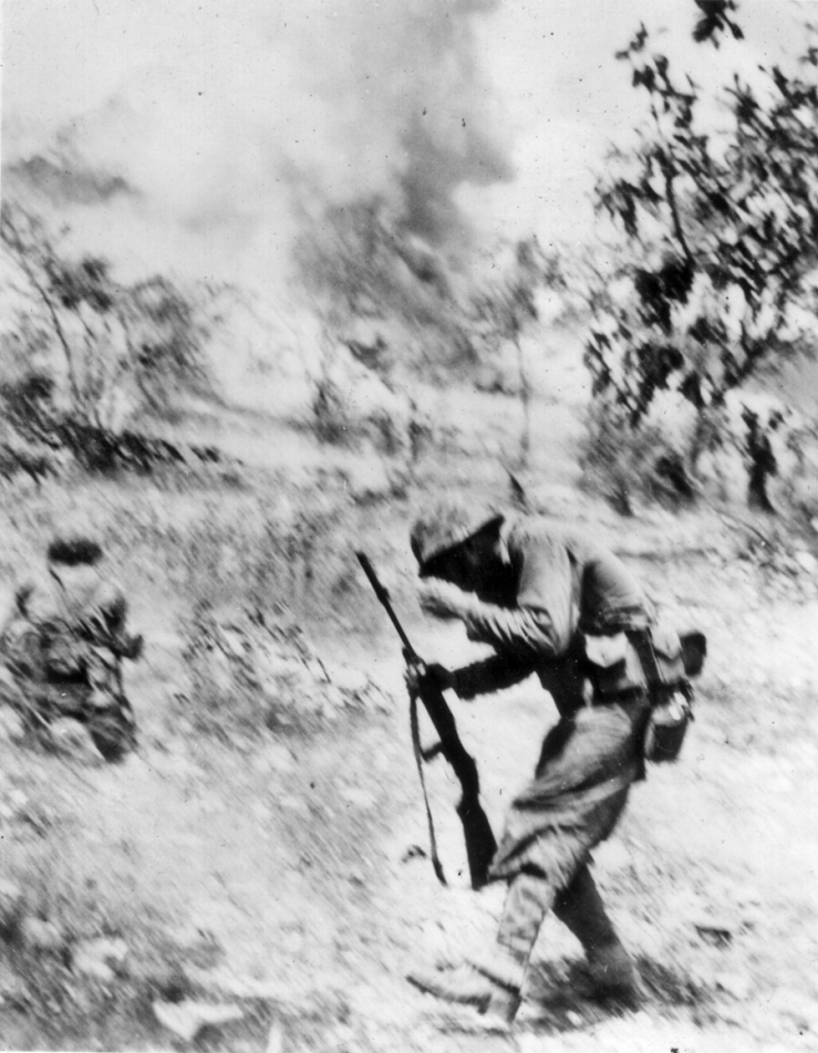 The photographer flinched while snapping this photograph - the plume of smoke in the background is an exploding mortar shell. The marine with the carbine was hit by shrapnel; some captions state he was killed by the blast.