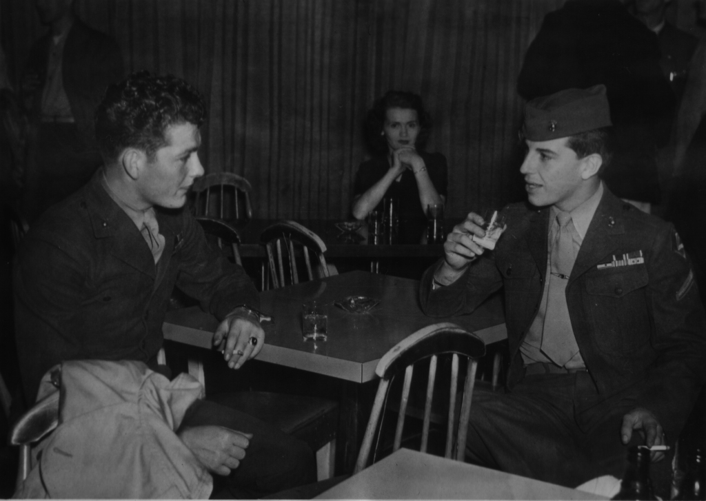Friends in war and in peace. Dues and Elissagaray catch up over a drink while a barfly in the background eyes the dashing young Marines.