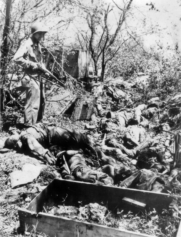 A marine overlooks a ditch full of dead Japanese troops.