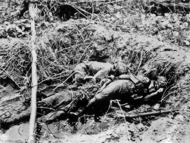 Dead Japanese troops in a waterlogged fighting hole.
