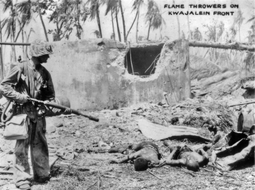 A marine with a flamethrower looks over a destroyed Japanese bunker, Kwajalein.