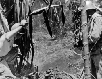 As one marine prepares to throw a smoke grenade, his buddy covers the cave opening with his carbine. Saipan, 1944.