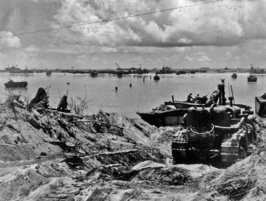 As the battle moved inland, support troops worked to improve the beachhead. Here, a bulldozer grades a path to help supply vehicles get off the beach.