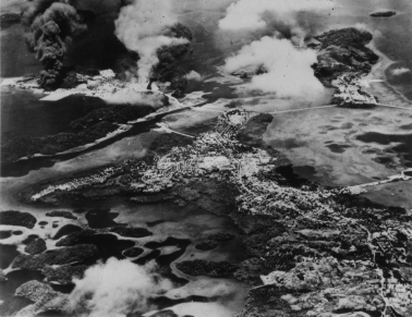 A Pacific island, probably an idyllic spot before the war, is marred by smoke and flames.