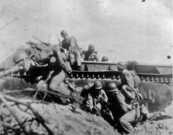 Marines debark from an LVT as one of their comrades accelerates over a slight rise on Guam.