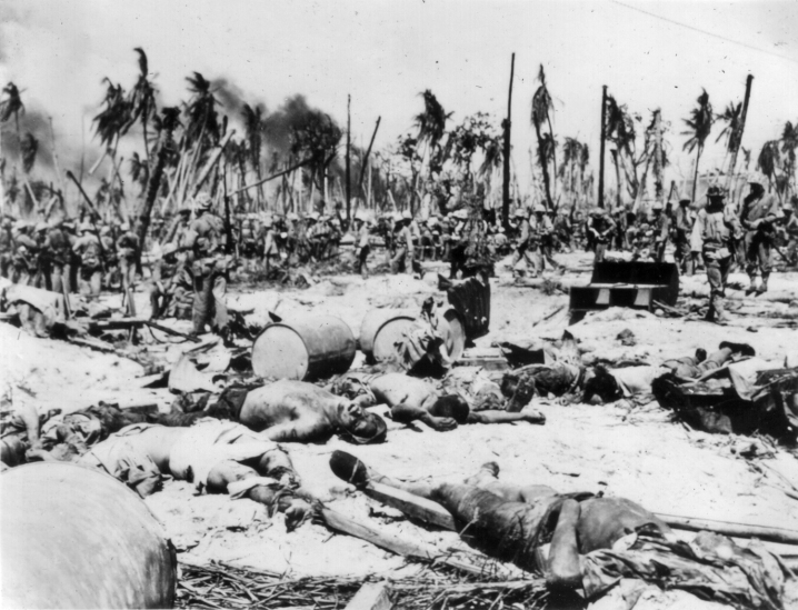 """INP Soundphoto. Some of 8,000 Japs who died on Kwajalein - Namur Island, Kwajalein Atoll.... Dramatic picture made after the fighting had ceased on Namur Island, showing hundreds of dead Japs littering the sandy ground near their blasted pillbox, while US Marines move up to the firing line in the background. 2-2-1944."""