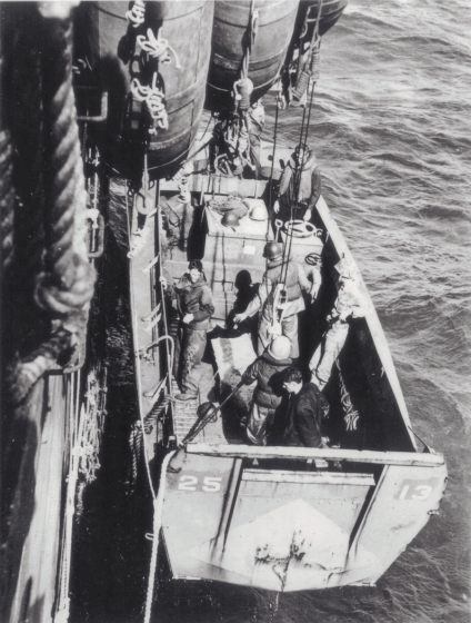 A Higgins boat is lowered over the side of its support ship.