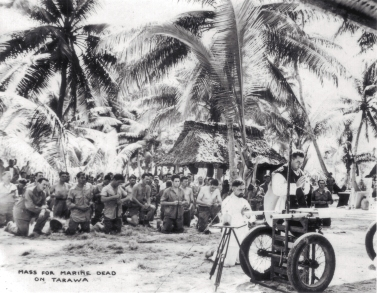 A chaplain, using two ammunition carts as an altar, says Mass for those killed on Tarawa.