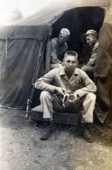 Walter Campbell of the machine gun platoon holds his canteen cup at the entrance to his tent.