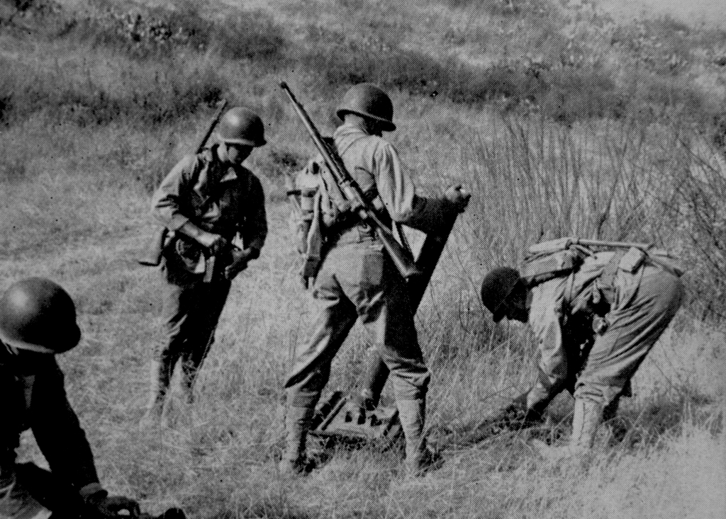 An 81mm mortar team races to set up their tube during training at Camp Pendleton, 1943. Note that the mortarmen are carrying the M1 rifle rather than the more portable carbine. In combat, carbines were often exchanged for the more reliable rifles - why these mortarmen, who have not yet been in combat, are carrying a heavier weapon is unknown.