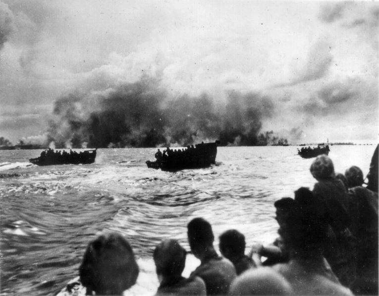 Sailors and support personnel watch from aboard ship as the assault waves are launched.