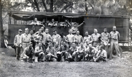 The assembled revelers in front of an abandoned trailer - with a mascot in a white cap at center in the front row.