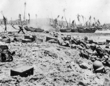 These Marines are pinned down on the beach. One man, at left, has found the courage or necessity to make a run forward.