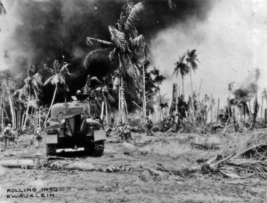 Army 7th Division troops - identified by the checkered panels on their backs - advance with a tank on Kwajalein.