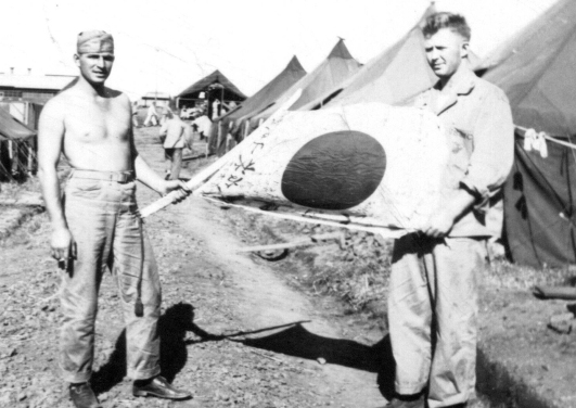Sandy and a friend display a Japanese sword and battle flag - souvenirs of Iwo Jima.