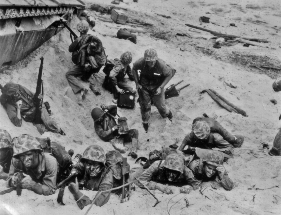 Marines crouch in a shellhole. The man standing at center may be a platoon or company commander establishing a CP.