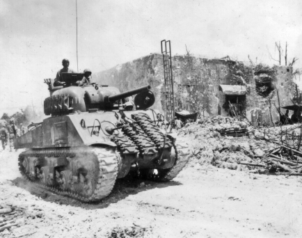 An M4 Sherman tank roars past an abandoned blockhouse.