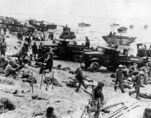 As a stretcher case is brought back (at left) supply personnel and Shore Party men organize the beachhead.