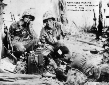 A signal unit of the 24th Marines in action on Namur, February, 1944. (UNIS markings on a lieutenant not visible in this version of the picture suggest they are from Third Battalion, 24th Marines).