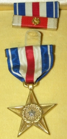 Ed DuBeck's Silver Star, awarded for the battle of Tinian. The other ribbon is unidentified but, with the chrysanthemum device attached, may have been Japanese.