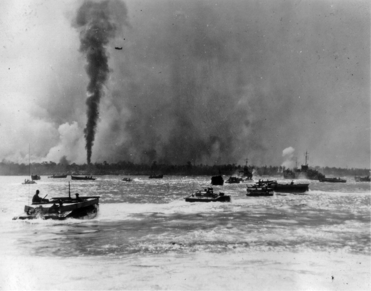 As a dive bomber passes overhead, LVTs bearing assault troops head for an island that is already shrouded in smoke.