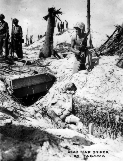 A tattooed Marine poses with a dead Japanese solder whom he has pulled out of the small bunker at left.