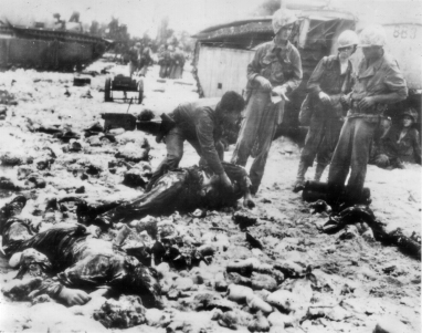 American troops on Peleliu search a body for identification.