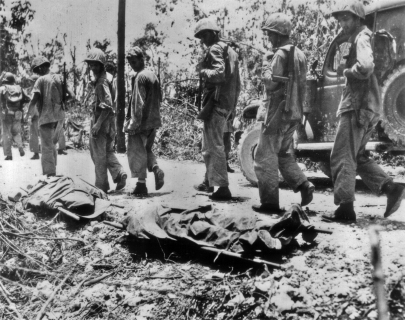 A distressing sight on the way to or from the lines - American dead laid out on stretchers.