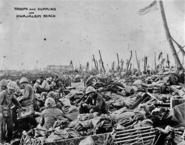 With the American flag flying proudly from a palm tree, supply and support personnel try to make sense of the mass of crates on a Kwajalein beach.