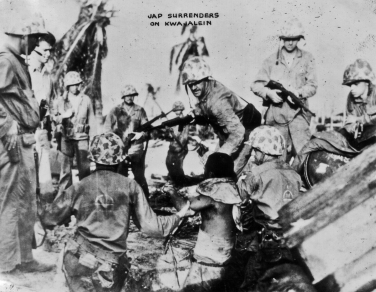 The enemy soldier is roughly hauled from his hiding place by marines on Roi.