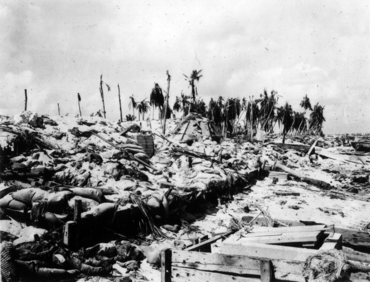 The aftermath of the Tarawa invasion. Bodies and supplies litter the beach, and a triangular steel pillbox at center has been knocked out.