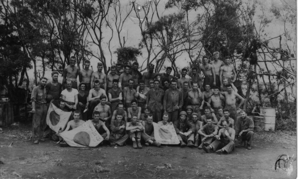 The survivors of Company A after securing Tinian. Buck Schechter is at center, wearing his utility blouse.