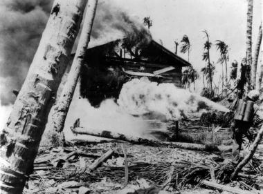 A Marine with a flamethrower destroys a Japanese building on Tarawa.