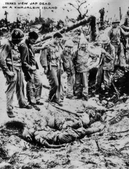 GIs take a look at dead Japanese on Kwajalein atoll.