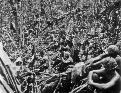 A platoon of marines gets The Word from their leader in the background at left. Peleliu, 1944.