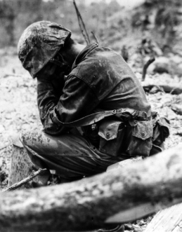 """""""This battle-worn Marine weeps from sheer fatigue as he rests briefly on a fallen tree trunk after he and fellow Leathernecks had wrested Hill 200 overlooking Peleliu Airport from the Japs in some of the bitterest fighting encountered by the Yanks in the Pacific. Photo by Stanley Troutman, NEA-ACME Newspictures, war correspondent for the war picture pool."""" Photo provided by Stan Troutman's daughter, Gayle, who adds: """"For this shot, I remember Dad telling me he purposefully did not shoot the Marine's face to give him privacy."""""""